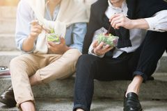 Healthy food outdoors. Male street style. Lunch break, two stylish unrecognizable young people, diet for modern men concept Stock Images