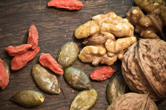 Healthy food pecan nuts, pumpkin seeds and goji berries on wooden background stock photo