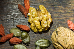 Healthy food pecan nuts, pumpkin seeds and goji berries on wooden background stock photography