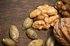 Healthy food pecan nuts and pumpkin seeds on wooden background stock image