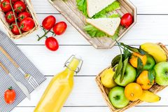 Healthy food for picnic. Sanwiches, fruits, vegetables, juice on tablecloth on white wooden background top view Royalty Free Stock Image