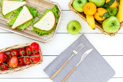 Healthy food for picnic. Sanwiches, fruits, vegetables on tablecloth on white wooden background top view Stock Photos