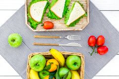 Healthy food for picnic. Sanwiches, fruits, vegetables on tablecloth on white wooden background top view Stock Photo