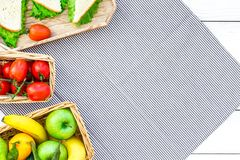 Healthy food for picnic. Sanwiches, fruits, vegetables on tablecloth on white wooden background top view copyspace Stock Photography