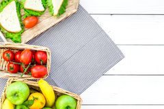 Healthy food for picnic. Sanwiches, fruits, vegetables on tablecloth on white wooden background top view copyspace Stock Images
