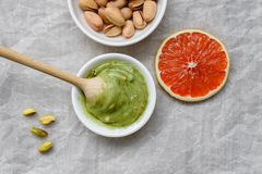 Healthy food, pistachio paste, peeled and unpeeled salted pistachios, grapefruit, wooden spoon on a light background. Components. For cooking royalty free stock photography