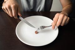 Healthy food, poverty, saving money: coins on a white plate at dining room. Knife and fork in the hands.  stock photos