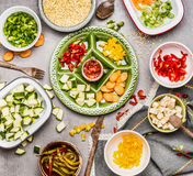 Healthy food preparation: gut colorful vegetables on green plate and bowls with barley seeds and feta Stock Image
