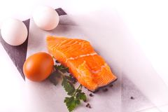 Healthy food, proteins, cooking and diet concept - close up of salmon fillet, eggs and parsley on white background. Healthy food, proteins, cooking and diet stock image