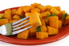 Healthy food - pumpkin. Pumpkin bites with dill seasonig on a red plate stock images