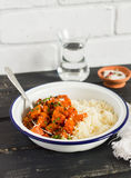 Healthy food - pumpkin stew and couscous in a white enamel bowl on a dark wooden Board. A vegetarian lunch. Royalty Free Stock Images