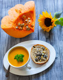Healthy food. Pumpkin vegetable soup and  bread with Chia seeds,  soy bean, pumpkin, pine and sunflower seeds Royalty Free Stock Photos