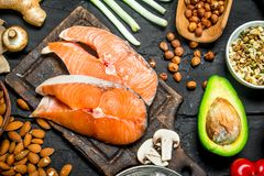 Healthy food. Raw salmon fish with organic food. On black rustic background stock images