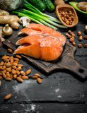 Healthy food. Raw salmon fish with organic food. On black rustic background royalty free stock images