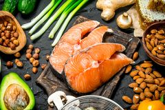 Healthy food. Raw salmon fish with organic food. On black rustic background stock photo