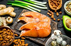 Healthy food. Raw salmon fish with organic food. On black rustic background royalty free stock photography