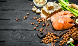 Healthy food. Raw salmon fish with organic food. On black rustic background royalty free stock image