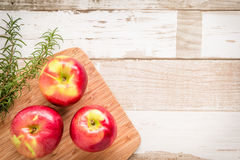 Healthy food: red apples and rosemary on wooden table. Healthy food arrangement with three red apples on a wooden board and rosmary leaves on a rustic wooden Stock Photo