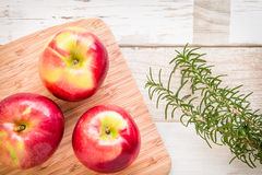 Healthy food: red apples and rosemary on wooden table. Healthy food arrangement with three red apples on a wooden board and rosmary leaves on a rustic wooden Stock Photography