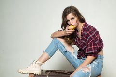 Healthy food. retro fashion model. teen girl in retro clothes. vintage style. denim look. hair fashion. travel with. Vintage suitcase. casual child in checkered royalty free stock images