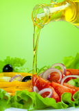 Healthy food salad and olive oil stream. Olive oil stream and healthy fresh vegetable salad Royalty Free Stock Photos