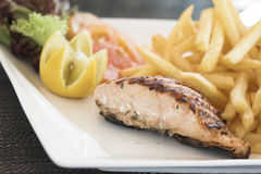 Healthy food, salmon steak and chips. Daily healthy meal, fish steak, vegetables and chips Royalty Free Stock Photography