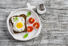 Healthy food - a sandwich with rye bread, soft cheese and boiled egg. On a light rustic wood surfaces. Stock Image