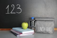 Healthy food for school child in lunch bag. And stationery on table near blackboard with chalk written numbers royalty free stock images