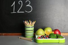 Healthy food for school child in lunch box. And stationery on table near blackboard with chalk written numbers stock image