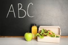 Healthy food for school child in lunch box on table near blackboard. With chalk written letters royalty free stock photos
