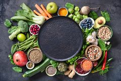 Healthy food selection with fruits, vegetables, seeds, super foods, cereals and the plate in the middle stock photo