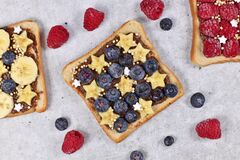 Slice of spelt toast bread topped with blueberry fruits, banana slices in shape of stars and puffed quinoa grain