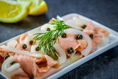 Slices of raw salmon marinated in lemon with green pepper and onion Royalty Free Stock Images