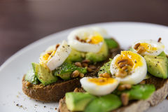 Healthy food snack of eggs and avocado on toasted bread. Healthy lifestyle snack on table Stock Photography