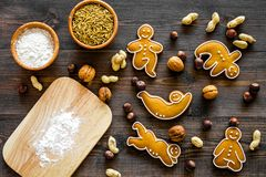 Healthy food for sportsman. Cookies in shape of yoga asanas near nuts on dark wooden background top view Stock Image