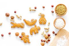 Healthy food for sportsman. Cookies in shape of yoga asanas near nuts on white background top view Stock Photos
