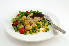 Healthy food, steak, potatoes and salad. Healthy restaurant diet food, steak, potatoes, salad, peas and corn with knife and fork on plate, on white, macro, close Stock Photography