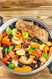 Healthy food, stewed pork meat with various colorful vegetables in pan on wooden background, top view Royalty Free Stock Photo