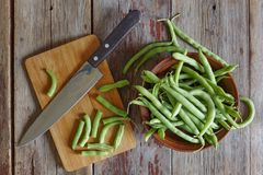Healthy food. String beans, raw asparagus in a clay bowl closeup. Top view on the wooden background Royalty Free Stock Images