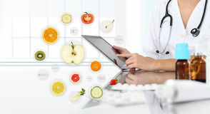 Healthy food supplements concept, Hand of nutritionist doctor to. Uch digital tablet on symbols fruits background Stock Image