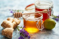 Healthy food table with different kinds of honey, fresh ginger and lime stock image