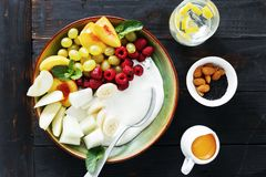 Healthy food table top view fruit breakfast natural yoghurt bowl. Healthy food concept on dark table, top view. Fruit breakfast and natural yoghurt bowl flat lay royalty free stock photography