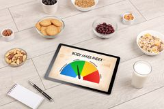 Healthy food with tablet on a wooden background royalty free stock photography