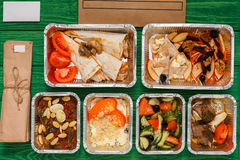 Healthy food take away in boxes, top view at green wood royalty free stock photos