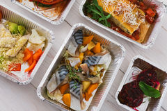 Healthy food take away in boxes, top view at wood. Healthy food delivery, daily ration. Take away of natural organic low carb diet. Fitness nutrition in foil Royalty Free Stock Photography