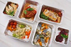 Healthy food take away in boxes, top view at wood. Healthy food delivery, daily ration. Take away of natural organic low carb diet. Fitness nutrition in foil Stock Photos