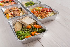 Healthy food take away in foil boxes on wood background Stock Photography