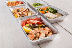 Healthy food take away in foil boxes on wood background Royalty Free Stock Photography