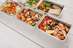 Healthy food take away in foil boxes on wood background Royalty Free Stock Photo