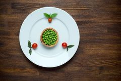 Healthy food theme: green peas on a plate with Royalty Free Stock Photography